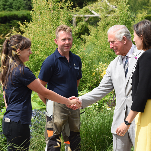 The Prince of Wales meets gardener Emma Bouchard with gardener Paul Eaton and garden designer Marie-Louise Agius right in the Centenary Garden SML squ