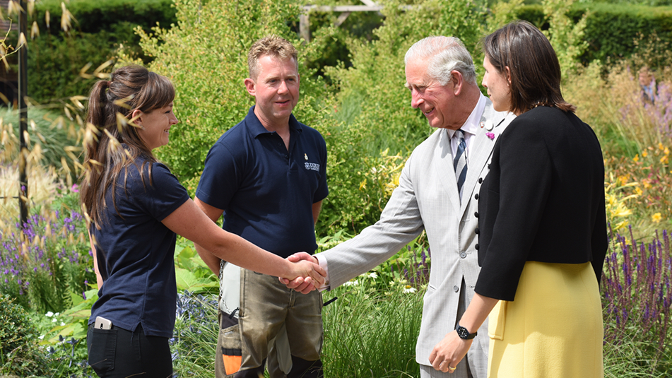 The Prince of Wales meets gardener Emma Bouchard with gardener Paul Eaton and garden designer Marie-Louise Agius right in the Centenary Garden SML